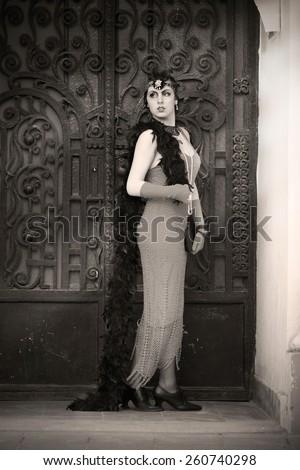 Full Length Portrait of The Beautiful Retro woman in Black Lace and Accessories in Style 1920s - 1930s Standing in the Old Metal Gate
