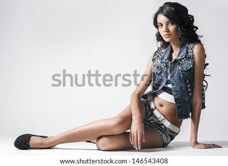 full-length portrait of the beautiful sexy young girl sitting and pose in studio - stock photo