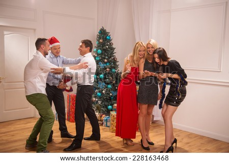 Full-length portrait of the company of friends celebrating the engagement of the lovely couple standing near the Christmas tree - stock photo