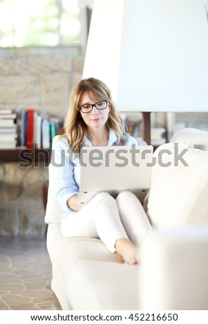 Full length portrait of thinking mature woman using her laptop while sitting on her couch at home.