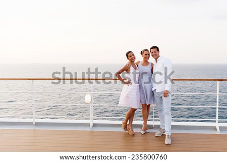 full length portrait of three friends standing on cruise ship deck - stock photo