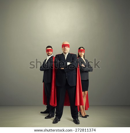 full length portrait of three superheroes in formal wear and red mask with cloak over light grey background - stock photo