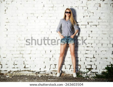Full Length Portrait of Trendy Hipster Girl with Hands in Pockets on White Brick Wall Background. Trendy Urban Fashion Concept. Copy Space. - stock photo