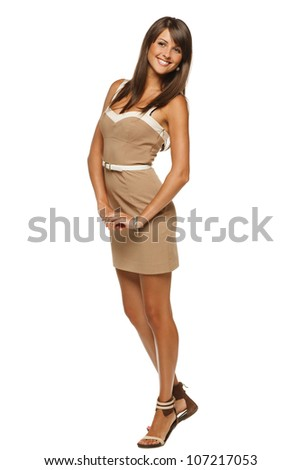 Full length portrait of trendy young woman in elegant beige dress posing against white background