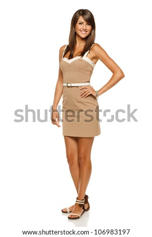 Full length portrait of trendy young woman in elegant beige dress smiling against white background