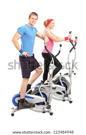 Full length portrait of two athletes on a cross trainer machine isolated on white background - stock photo
