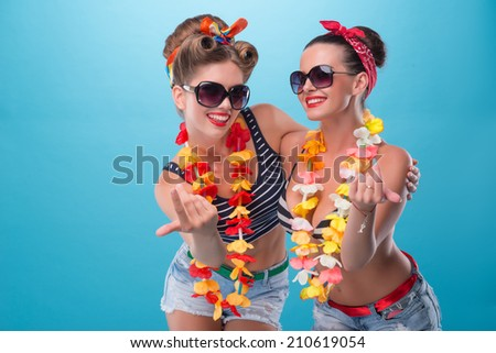 Full length portrait of two beautiful emotional coquette sexy girls with pretty smiles in pinup style with Hawaiian flowers necklaces, inviting somebody with finger isolated on blue - stock photo
