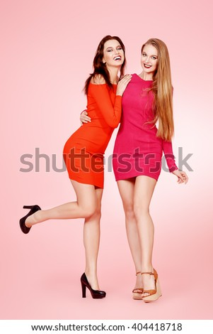 Full length portrait of two beautiful young women in red dresses posing together. Beauty, fashion. - stock photo