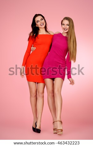 Full length portrait of two beautiful young women in red dresses posing together. Beauty, fashion.