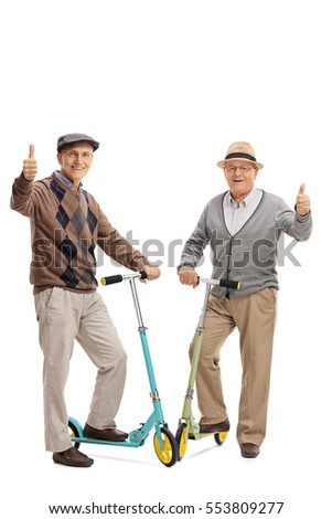 Full length portrait of two cheerful elderly men with scooters giving thumbs up isolated on white background