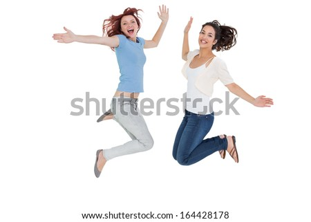 Full length portrait of two cheerful young female friends jumping over white background