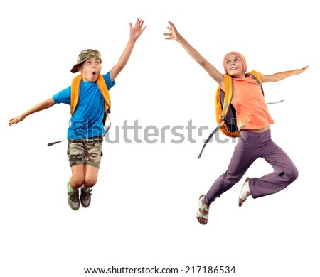 Full length portrait of two children with backpacks jumping and trying to reach something together. Isolated over white background - stock photo