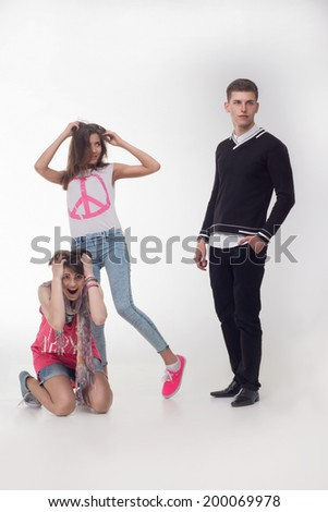 Full length portrait of two excited teenage girls screaming and looking with admiration and desire on a cute handsome boy, isolated on white background. Concept of love, youth, relationship - stock photo