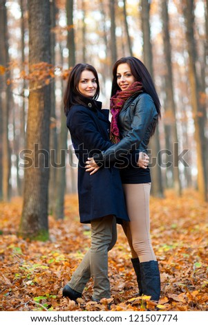 Full length portrait of two girlfriends hugging in the woods - stock photo