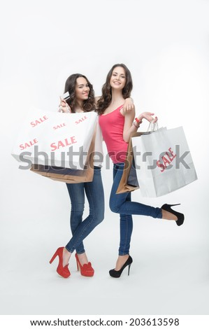 Full length portrait of two pretty girls showing us beauty of their cool bootees and holding many packages from the mall. Isolated on the white background