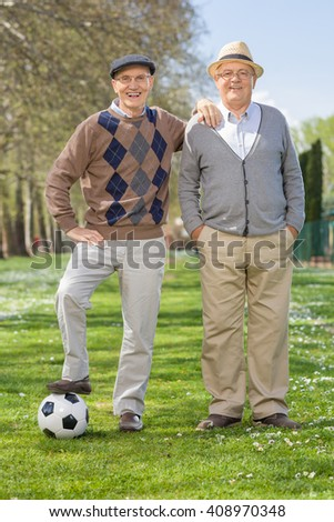 Full length portrait of two senior gentlemen posing in a park with a football on a sunny day - stock photo