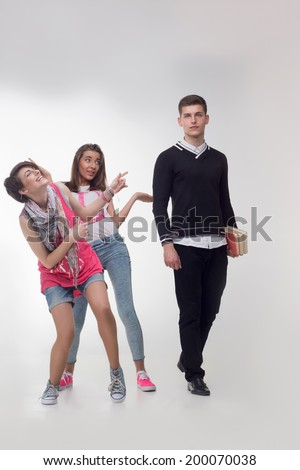 Full length portrait of two teenage girls are teasing the teenager with books. Girls are pointing and laughing at a cute handsome boy, isolated on white background. - stock photo