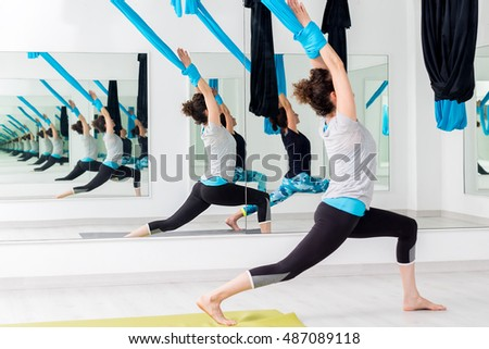 Full length portrait of two women practicing aerial yoga in studio.