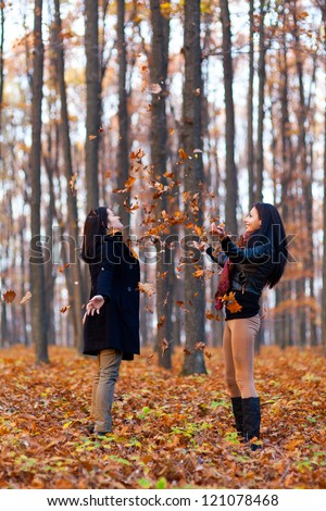 Full length portrait of two young girlfriends playing with dried leaves in the woods - stock photo