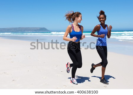 Full length portrait of two young woman smiling and running on the sea shore