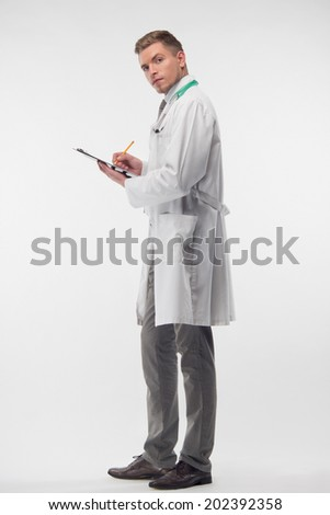 Full length portrait of very attractive doctor, wearing white coat and having the stethoscope, standing sideways and writing names of new patients in his notebook. Isolated on the white background