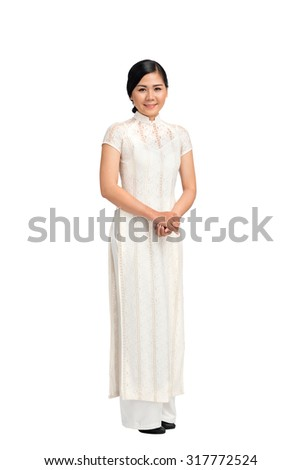 Full-length portrait of Vietnamese girl in ao-dai dress, isolated on white
