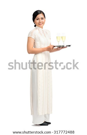 Full-length portrait of Vietnamese waitress carrying tray with champagne glasses