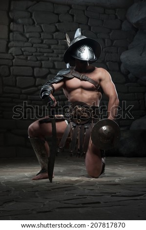 Full length portrait of warrior gladiator with muscular body in helmet holding sword, kneeling on dark background. Concept of masculine power, strength - stock photo
