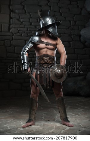 Full length portrait of warrior gladiator with muscular body in helmet holding sword on dark background. Concept of masculine power, strength - stock photo