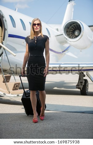 Full length portrait of wealthy woman with luggage walking against private jet at airport terminal - stock photo