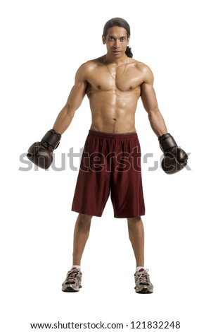 Full length portrait of well built male boxer wearing brown boxing gloves against white background