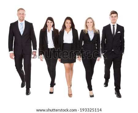 Full length portrait of welldressed businesspeople walking against white background - stock photo