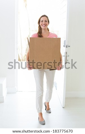Full length portrait of woman carrying cardboard box in new house - stock photo