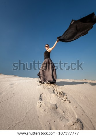 Full length portrait of woman in long dress holding long cloth on sand dune