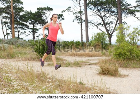 Full length portrait of woman jogging on trail outside with both feet off the ground