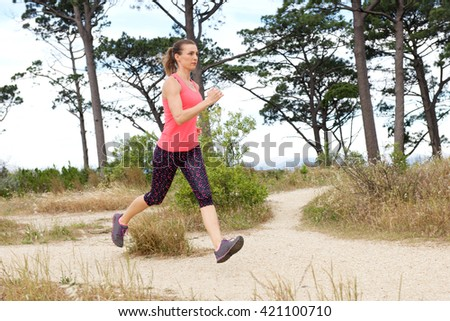 Full length portrait of woman running outside with both feet off the ground