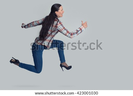Full length portrait of woman running sideways. Isolated over gray - stock photo