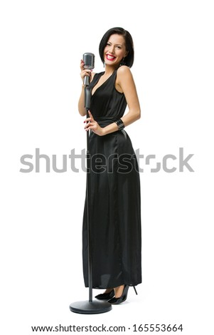 Full-length portrait of woman singer wearing long black evening dress and holding microphone - stock photo