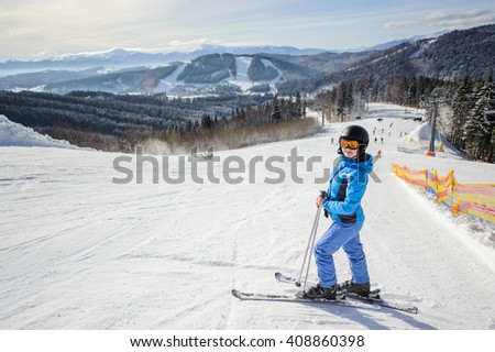 Full length portrait of woman skier resting in the middle of ski slope against ski lift and beautiful winter landscape background. Ski resort. Winter sports concept. Carpathian Mountains, Bukovel - stock photo