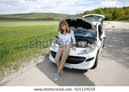 Full length portrait of woman standing her breaking down car and calling roadside assistance.  - stock photo