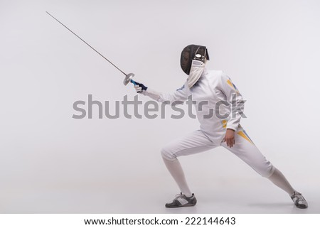 Full-length portrait of woman wearing white fencing costume and black fencing mask practicing with the sword. Isolated on white background