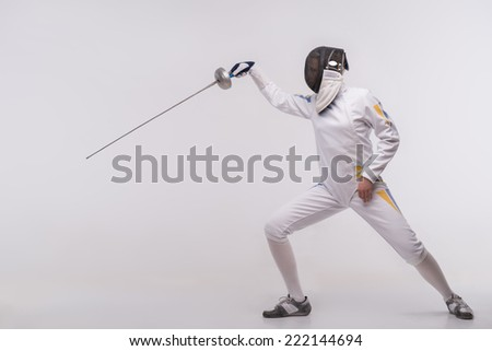 Full-length portrait of woman wearing white fencing costume and black fencing mask practicing with the sword. Isolated on white background - stock photo