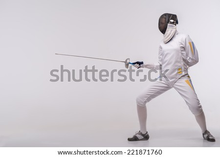 Full-length portrait of woman wearing white fencing costume and black fencing mask standing with the sword practicing in fencing. Isolated on white background - stock photo