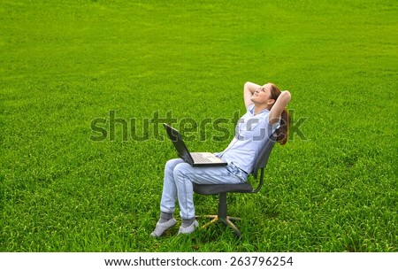 Full length portrait of young adult girl with black laptop sitting and relaxing in chair a field on fresh green spring summer grass field meadow Woman enjoy and relaxing outdoor nature scene - stock photo
