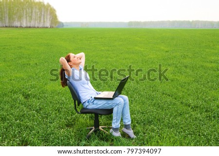 Full length portrait of young adult girl with black laptop sitting and relaxing in chair a field on fresh green spring summer grass field meadow. Woman enjoy and relaxing outdoor nature scene