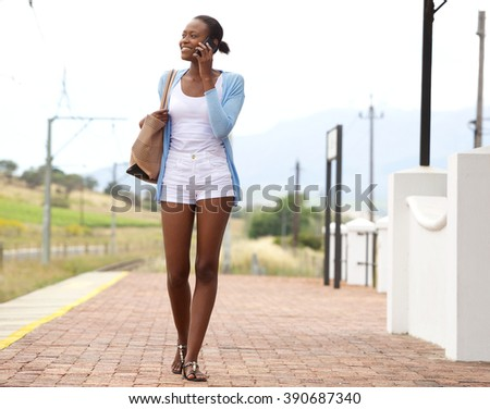Full length portrait of young african woman at railway station making a phone call  - stock photo