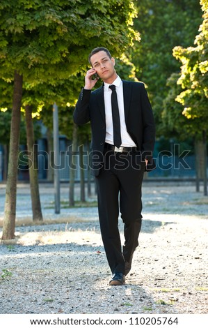 Full length portrait of young attractive businessman talking on mobile phone outdoors. Caucasian man walking and wearing a black business suit. - stock photo