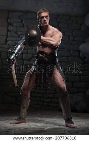 Full length portrait of young attractive warrior gladiator with muscular body holding shield and axe, posing on dark background. Concept of masculine power, strength