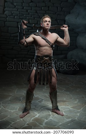 Full length portrait of young attractive warrior gladiator with muscular body posing with sword on dark background. Concept of masculine power, strength