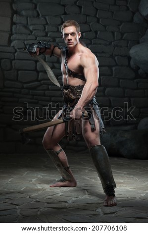 Full length portrait of young attractive warrior gladiator with muscular body posing with two swords on dark background. Concept of masculine power, strength - stock photo